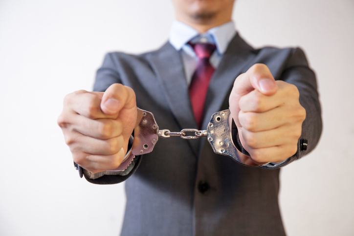 man in suit in handcuffs