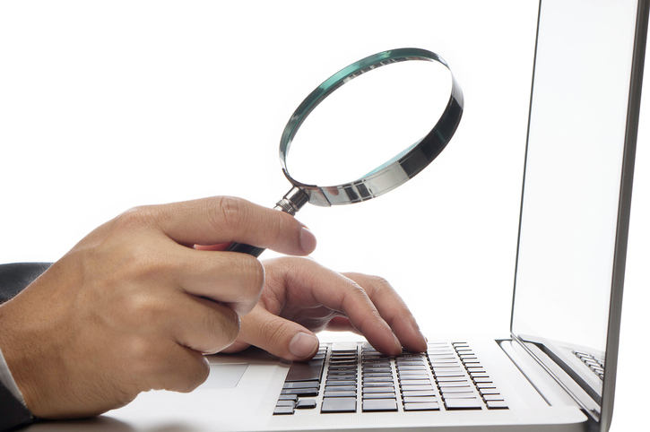 looking through magnifying glass at computer screen