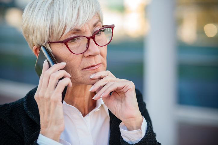 Worried mature businesswoman talking on the mobile phone