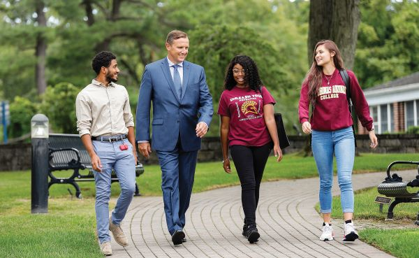 Ken Daly walking with students on campus