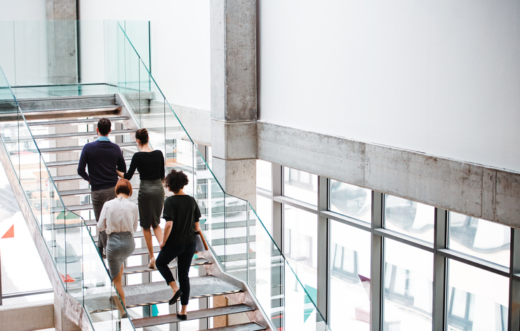 businesspeople walking up glass staircase