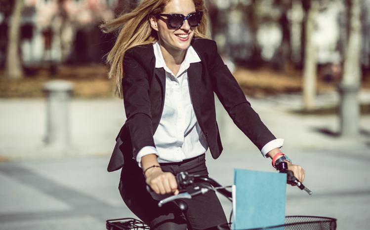 Mujer sonriente con gafas de sol montando en bicicleta.