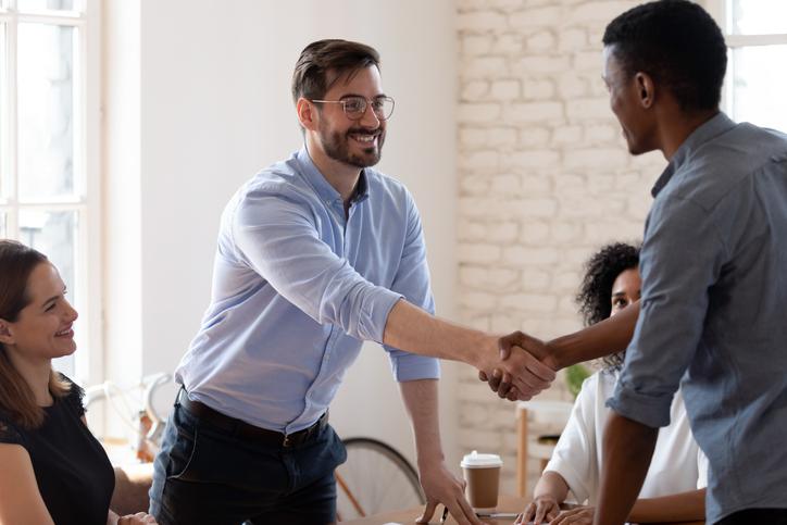 Dos hombres se dan un apretón de manos en una reunión.