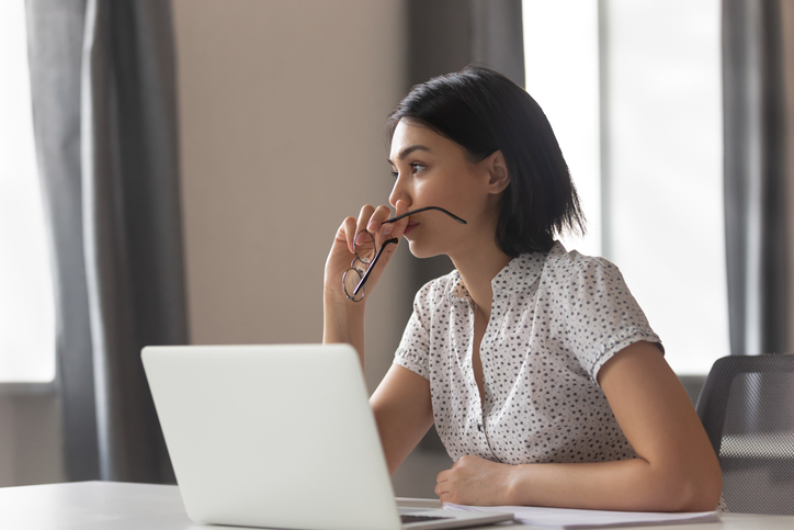 woman sitting at computer looking pensive