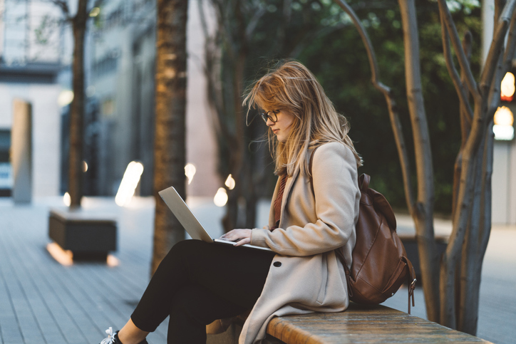 woman sitting on bench with open laptop