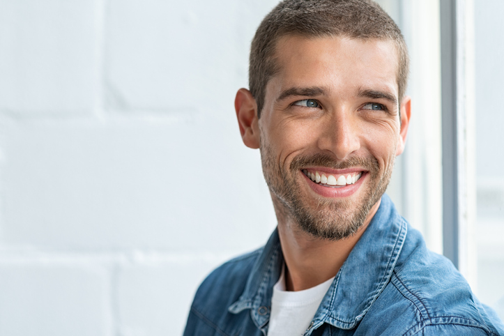 Confident young man looking away with big smile