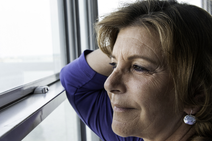 mature woman smiling while looking out a window