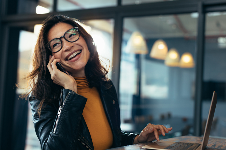 Business woman making a phone call and laughing