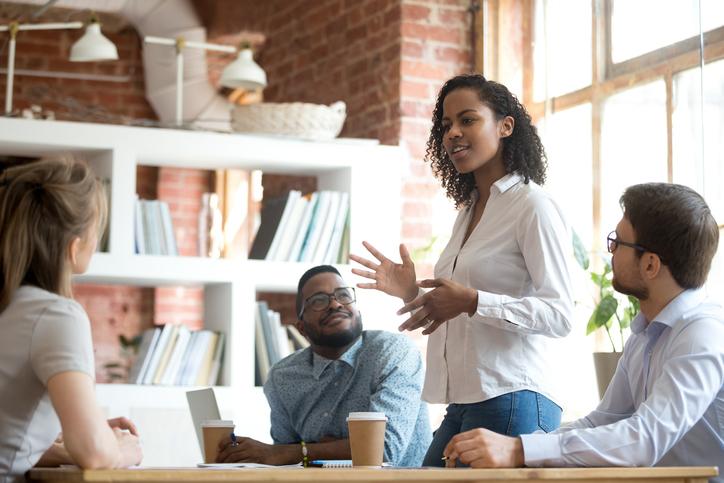 smart female employee speaking at diverse meeting
